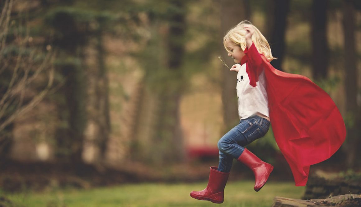 Little girl with cape jumping off deck in forest
